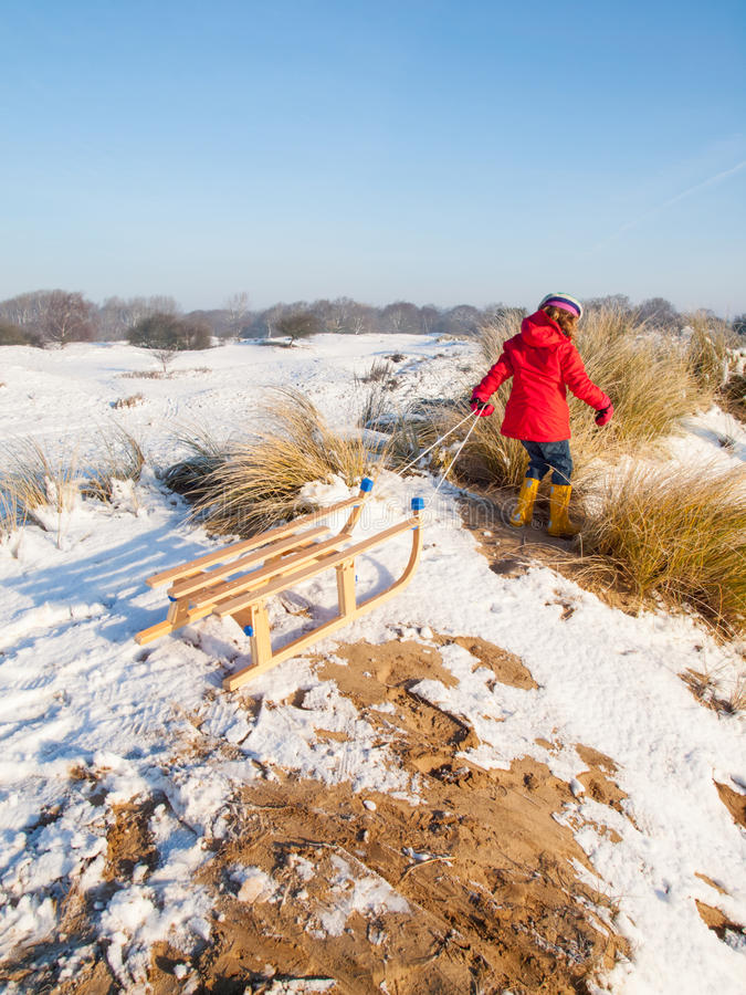 Small with a wooden sledge royalty free stock photo