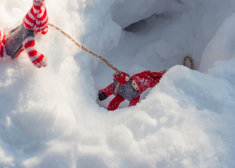 Small wooden toys in the rescue scene and assist. Doll pulls a rope from a snowy ravine another doll royalty free stock images