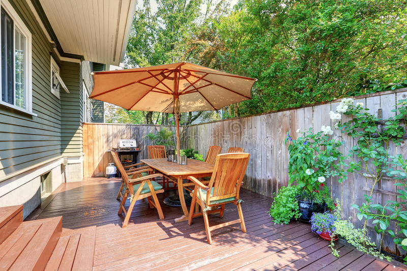 Small wooden walkout deck and patio table set with umbrella stock photo