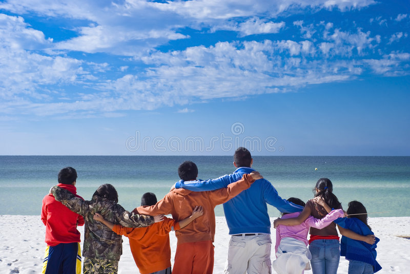 Small world. Picture of kids of different shapes, ages, sizes and ethnicities hand in hand signifying unity, peace and love. They look into the horizon to stock photos