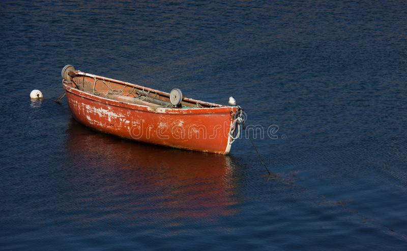 A Small Boat at Peggy`s Cove. A small, worn, red boat at Peggy`s Cove in Nova Scotia, Canada royalty free stock photography