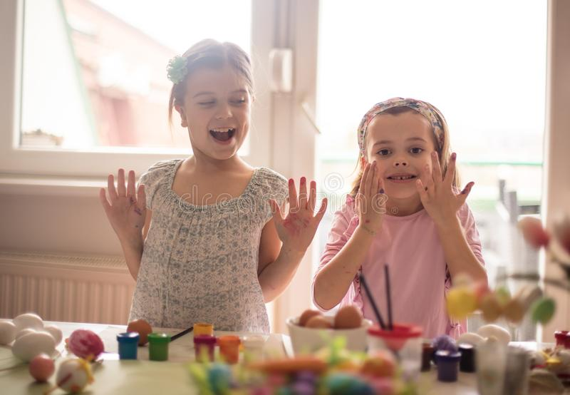 Small worthy hands. Little girls coloring Easter egg stock photography