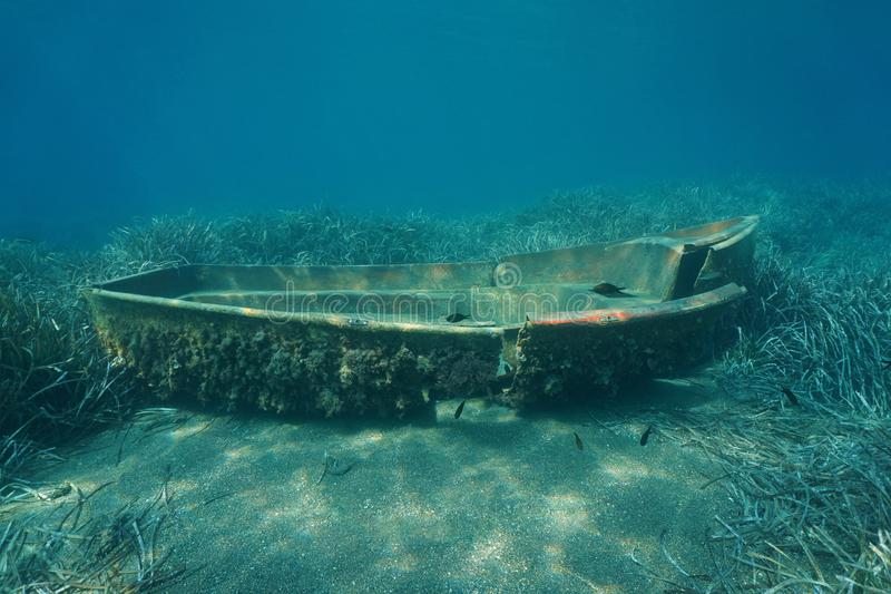 A small wrecked boat underwater on the seabed royalty free stock images