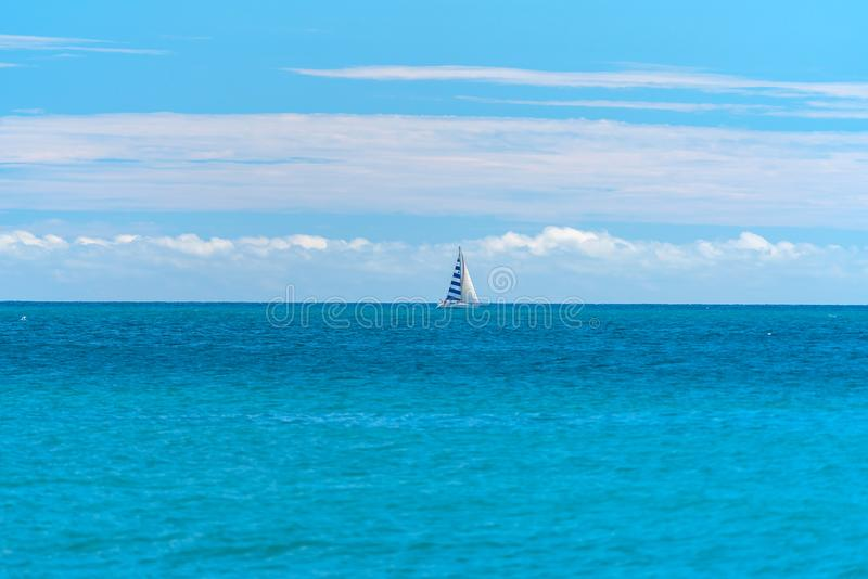 Small yacht under sail in the open sea stock images