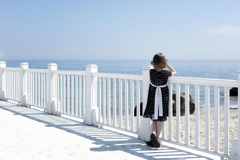 Small 7 years old pretty cheerful girl in a black  dress with white polka dots is standing on a wooden white pier royalty free stock photos