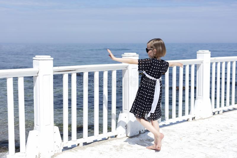 Small 7 years old pretty cheerful girl in a black  dress with white polka dots is standing on a wooden white pier stock photography