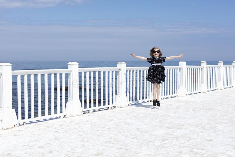 Small 7 years old pretty cheerful girl in a black  dress with white polka dots is standing on a wooden white pier royalty free stock images