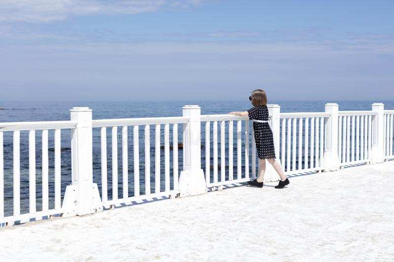 Small 7 years old pretty cheerful girl in a black  dress with white polka dots is standing on a wooden white pier royalty free stock photo