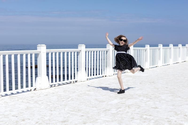 Small 7 years old pretty cheerful girl in a black  dress with white polka dots is standing on a wooden white pier stock image