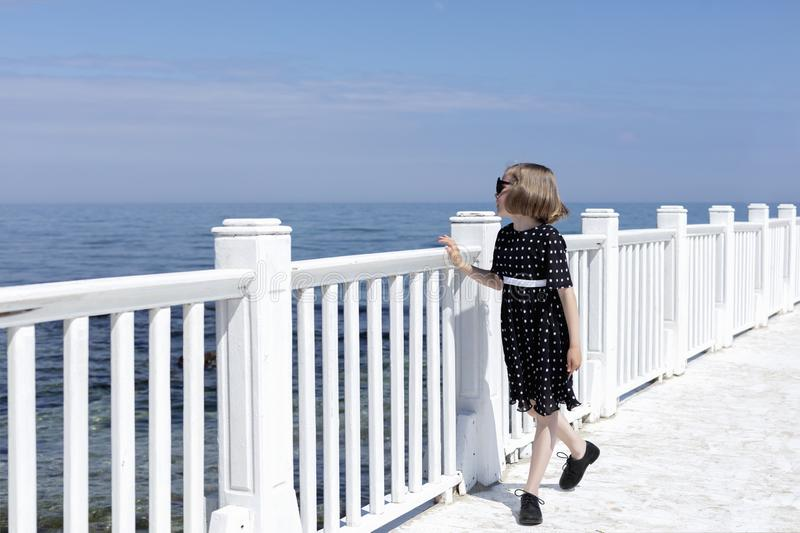 Small 7 years old pretty cheerful girl in a black  dress with white polka dots is standing on a wooden white pier royalty free stock photography
