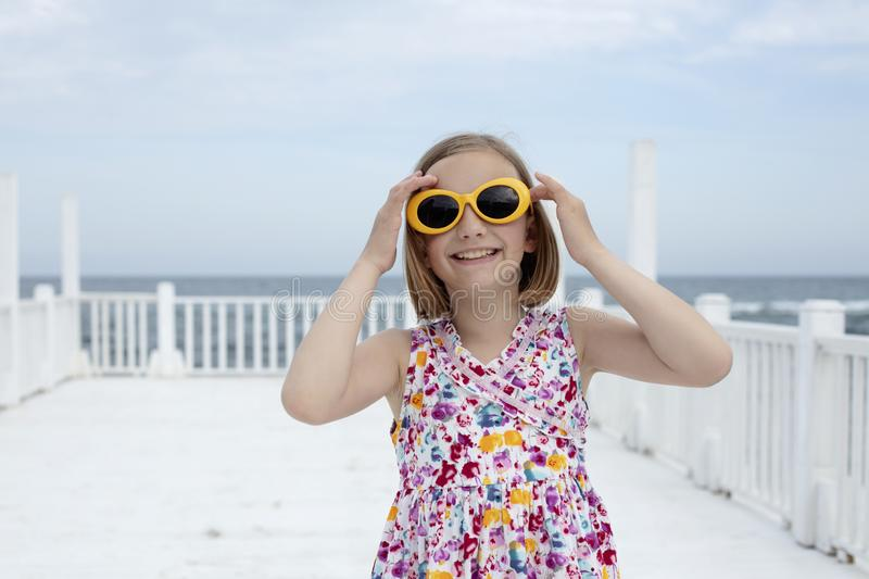 Small 8 years old pretty cheerful girl in a dress with a floral print and in yellow sunglasses stands on a wooden white pier stock photos