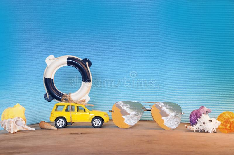 Small yellow car with lifebuoy on blue background stock photo