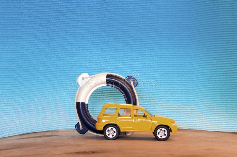 Small yellow car and lifebuoy on blue background stock images