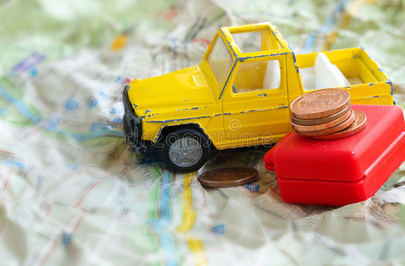 Small yellow car,suitcase and euro coins on a map. Mini yellow car with red suitcase and coins on a jammed map. Closeup cents royalty free stock images