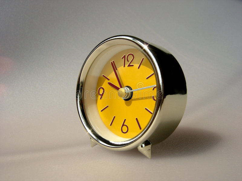 A small yellow clock (retro style) stock photos
