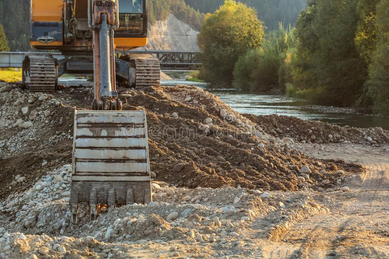 Small yellow excavator at pile of rocks and stones next to river, detail on digger bucket on ground. Construction at riverside stock photo