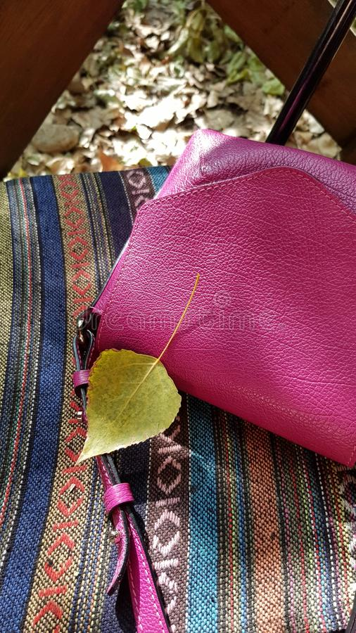 Small yellow leaf on fuchsia color leather handbag. On folk ornaments background. Natural fall leaf closeup on weaving fabric rug. Bright colors of fall season stock photography