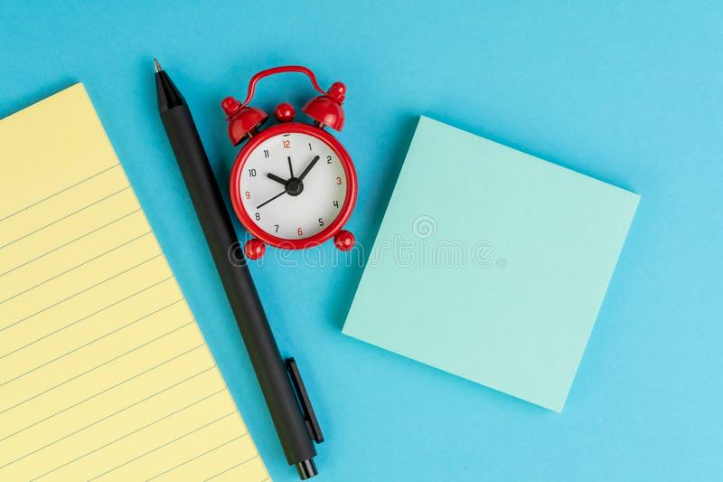 Small yellow paper notepad with blank page, alarm clock, pen and sticky note on solid blue background using as meeting note, royalty free stock photography