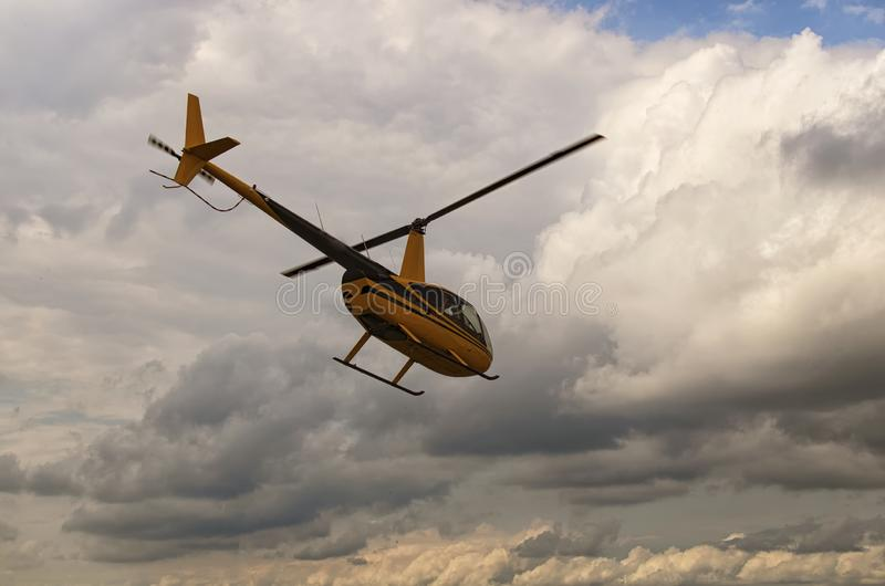 A small yellow private helicopter flies in the direction of thunderclouds. A small private airfield in Zhytomyr, Ukraine.  stock photo