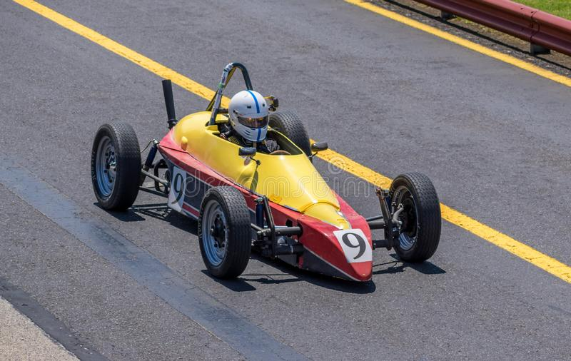 Small yellow and red vintage racing car stock photos