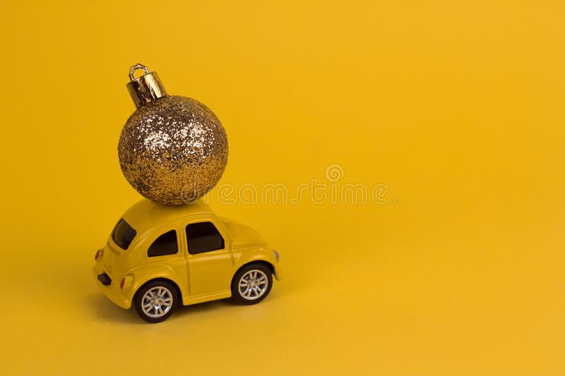 yellow retro car carries a golden christmas ball on a yellow copy space background stock photo