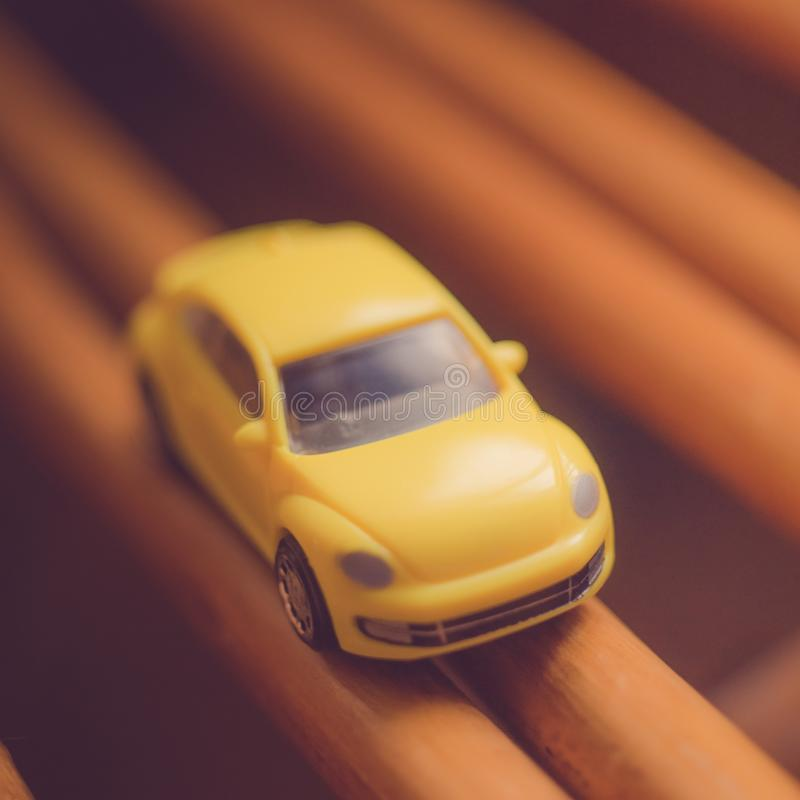 Small yellow toy car on the brown road.  stock images