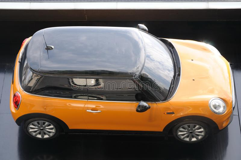 A small yellow two door car stock image