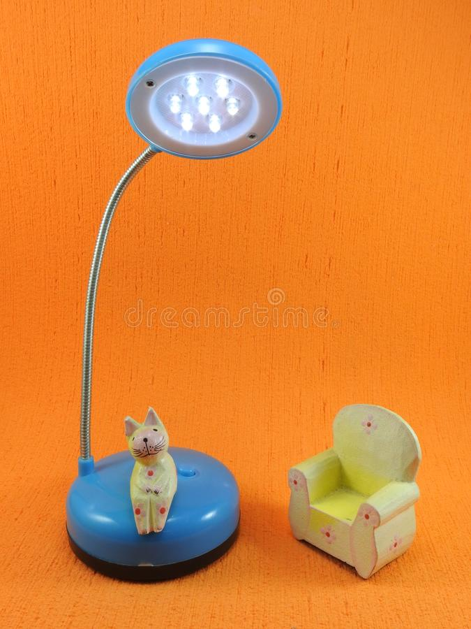 Small yellow wooden cat sitting on a led desk lamp next to a small wooden chair. royalty free stock image