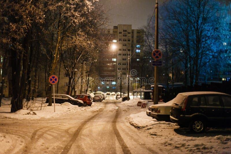 Smalle die straat in sneeuw in de avond wordt behandeld geparkeerde auto's royalty-vrije stock afbeeldingen