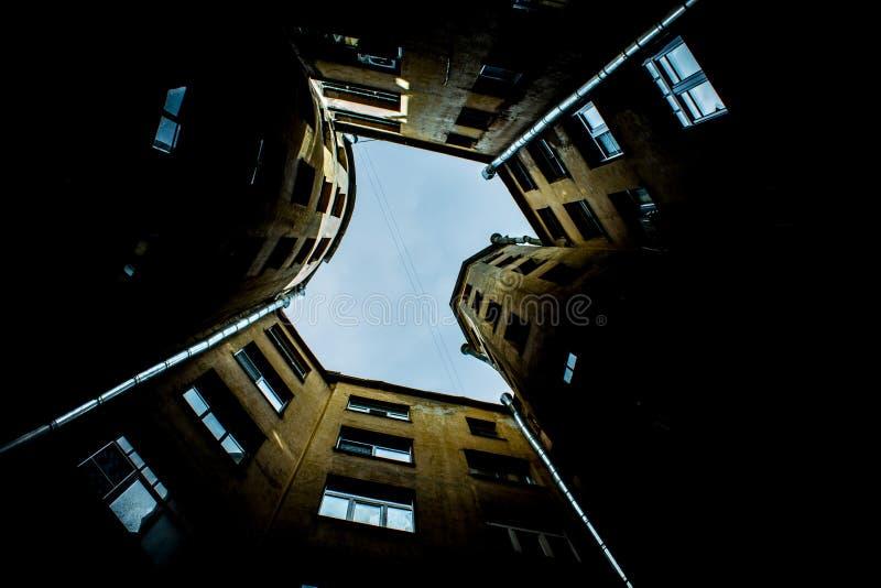 Smalle gebouwen goed in heilige-Petersburg met de hemel boven de daken Onder mening stock foto's