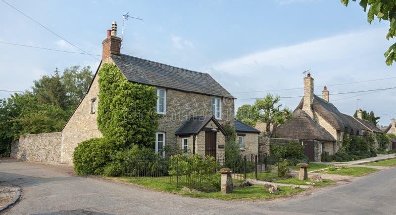 Smalle steeg met romantische met stro bedekte huizen en steenplattelandshuisjes in het mooie dorp van Munsterlovell, Cotswolds, O stock afbeelding