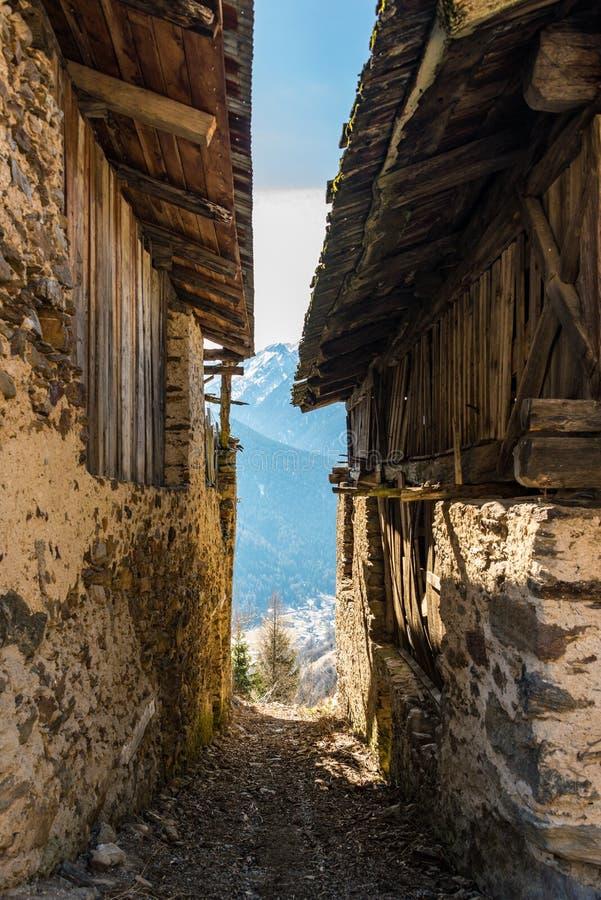 Smalle steeg tussen oude huizen met bergmening stock foto's