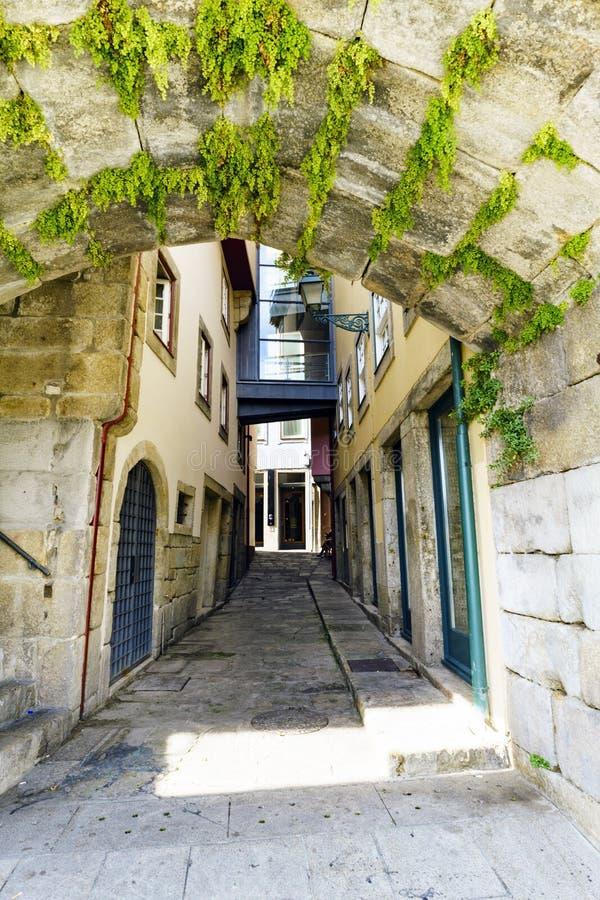 Smalle steeg van keien met een steentunnel met kruiden bij het begin en solitaire voorgevels van oude huizen, en zonder winkels stock afbeelding