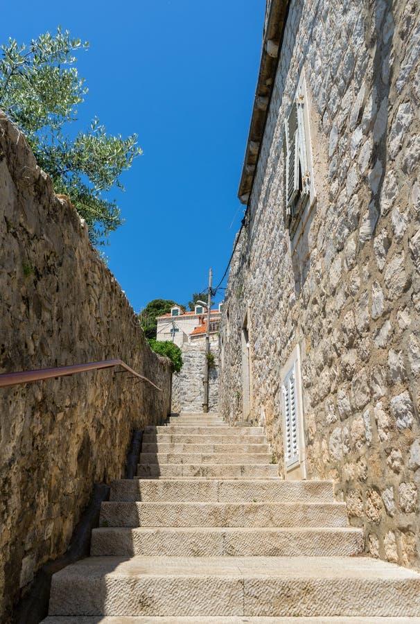 smalle steentreden tussen oude woonwijk in Kroatië Adriatisch kustdorp met steenhuizen en Oude steenstraat van stock afbeelding