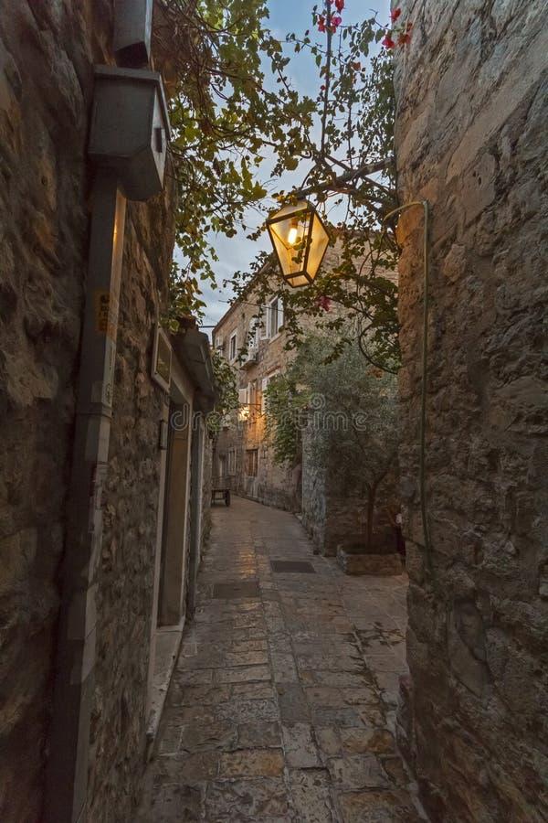 Smalle straat in de oude Budva-nacht met wijnoogst  stock fotografie