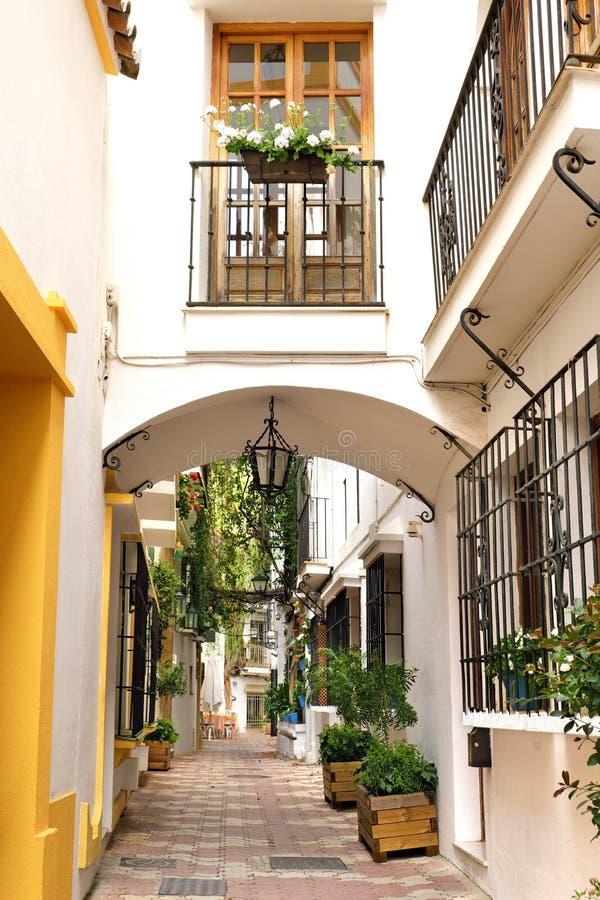 Smalle straat en huizen met boog in oude stad van Marbella, Spanje stock foto's