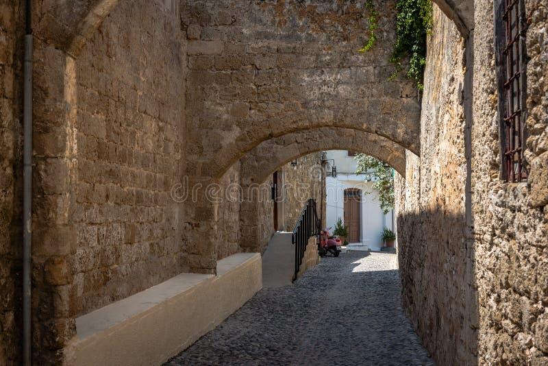 Smalle straat met oude middeleeuwse bogen in het slepen van Rhodos Het eiland van Rhodos, Griekenland stock foto