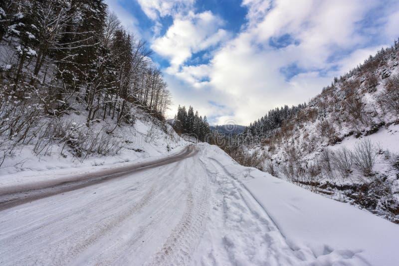 Smalle windende bergweg in sneeuw, dag de winterlandschap met blauwe bewolkte hemel royalty-vrije stock afbeeldingen