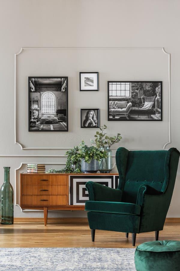 Smaragdgroene leunstoel in woonkamer met zwart-witte foto's op grijze muur en retro kabinet stock foto