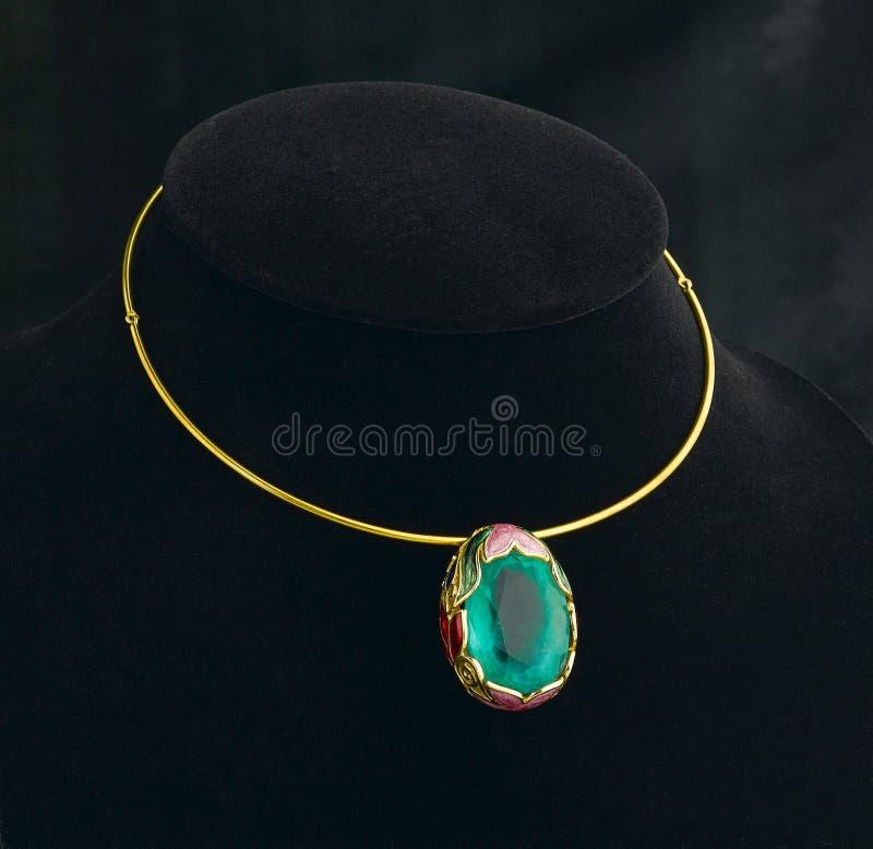 Smaragdhänge och guld- halsband royaltyfria foton