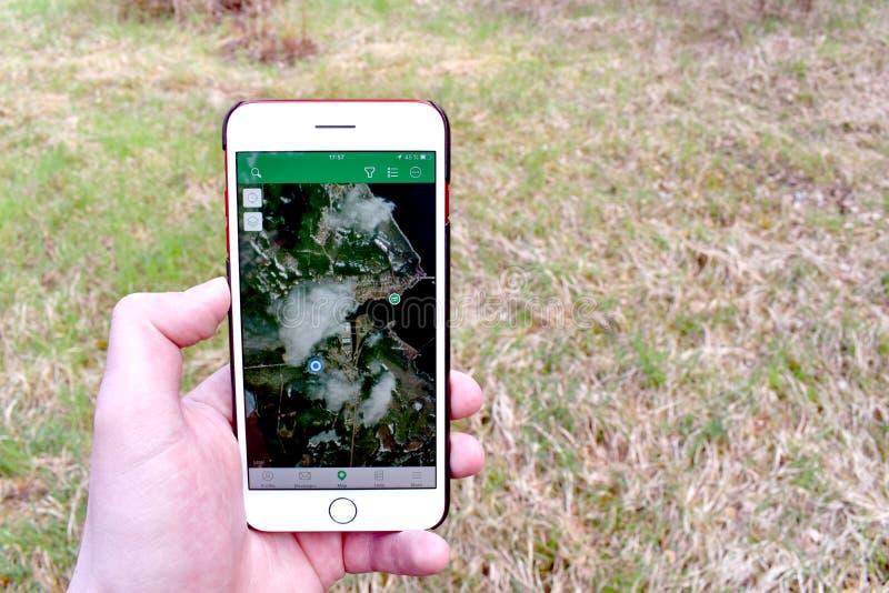 Smarphone da terra arrendada da mão com mapa geocaching e um esconderijo indicado nele imagens de stock royalty free