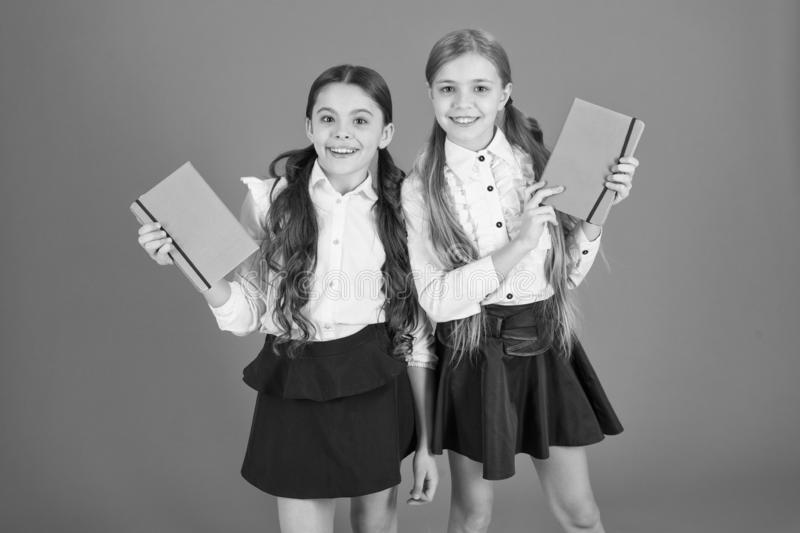 Smart and adorable. Cute schoolgirls holding lesson books. Little children with school diaries for making notes. School royalty free stock images