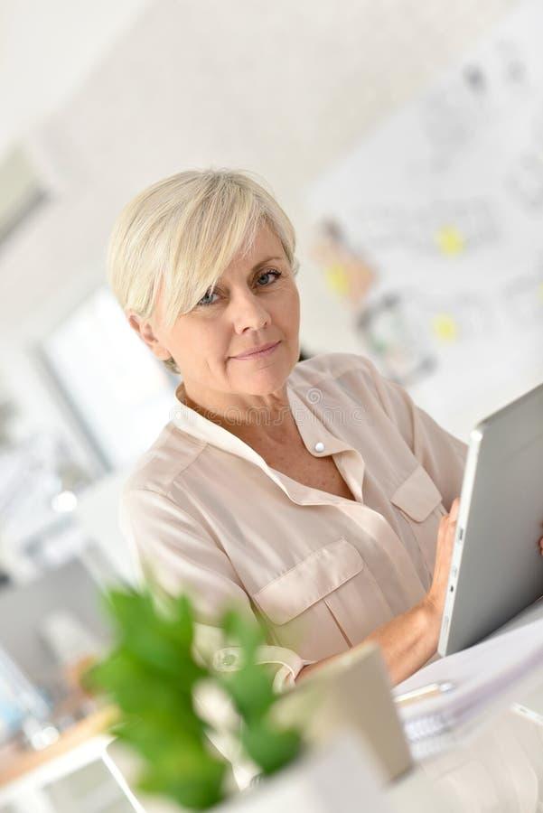 Smart affärskvinna för pensionär som arbetar på bärbara datorn royaltyfri bild