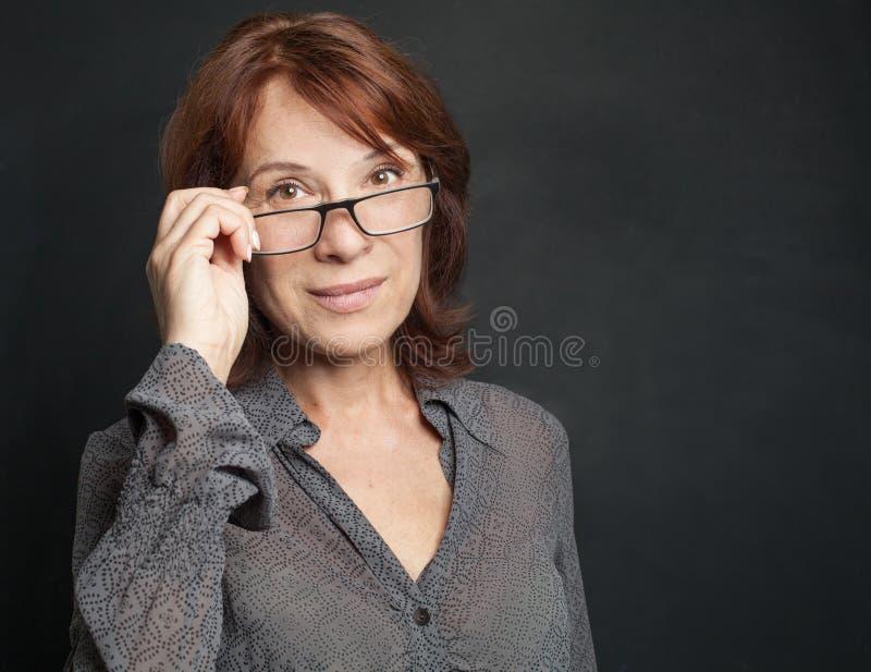 Smart affärskvinna i exponeringsglas på mörk bakgrund royaltyfria bilder