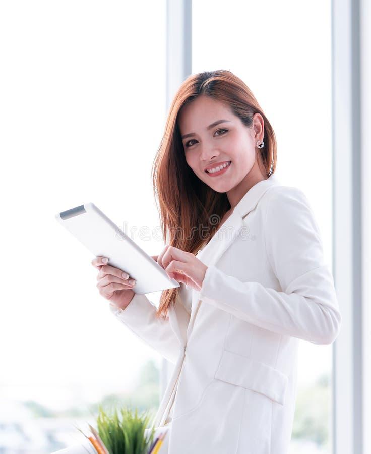 Smart affärskvinna som använder minnestavlan vid fönstret arkivfoto