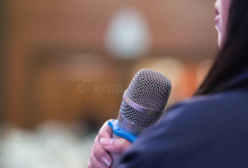 Smart affärskvinnaanförande eller att tala med mikrofonen i seminariumkorridoren, handen som gör en gest att protestera eller tro arkivbilder