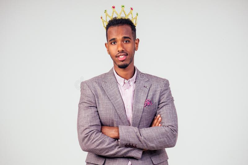 Smart african american successful and rich businessman in a stylish suit and the golden crown on his head on white stock photos