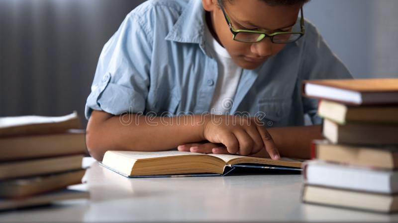 Smart Afro-American boy reading books, bookworm kid, little nerd, education royalty free stock images