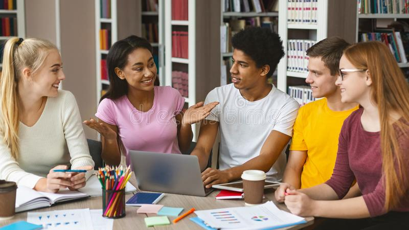 Smart afro girl sharing her creative ideas with friends. Smart african american girl sharing her creative ideas with other students. Studying together in campus stock image