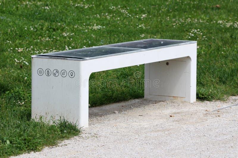 Smart allmänhet parkerar bänken med det förstörda van vid maktbatteriet för solpanelen som används för uppladdning av mobiltelefo royaltyfri foto